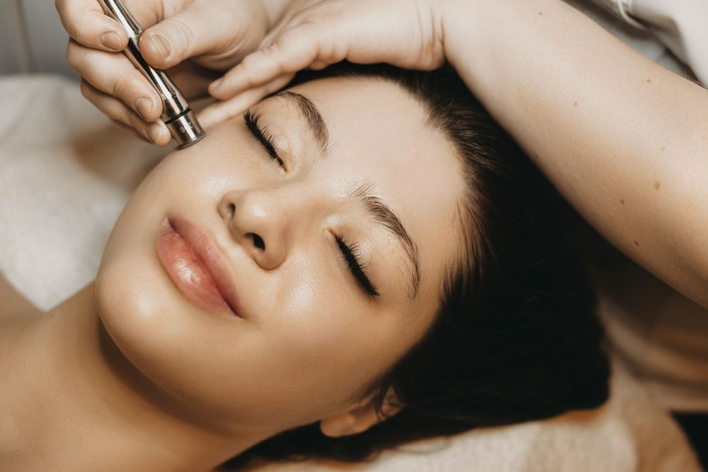 Close up of a lovely caucasian woman having microdermabrasion non invasive therapy with derma pen in a wellness center.